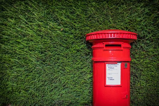 Classic Red British Pillar Box Against Hedge