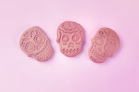 Day of the Dead concept. Three ginger cookies in the shape of skulls, shot from the top on a pink background with a place for text