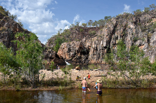 People swimming in the waterhole at Edith Falls, which is a series of cascading waterfalls and pools on the Edith River in the Nitmiluk National Park, Australia.