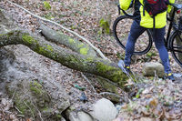 carry the bike through the log, the cyclist in the forest through the windbreak, carry the bike thro