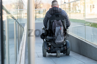 Man in a electric wheelchair using a ramp