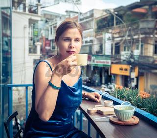 Beautiful woman enjoying tea on cafe terrace