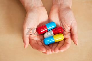 Hände halten drei große Pillen oder Medikamente