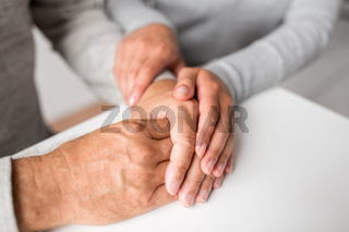 close up of young woman holding senior man hands