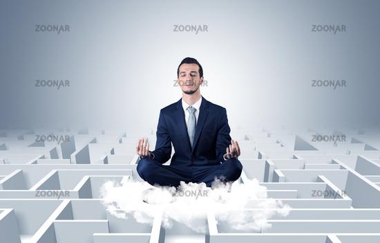 Businessman meditates on a cloud with maze concept