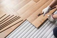 Installing laminated floor, detail on man hands holding hammer in textile gloves, over white foam base layer
