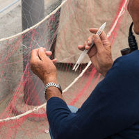 Fisherman is fixing a fishing net