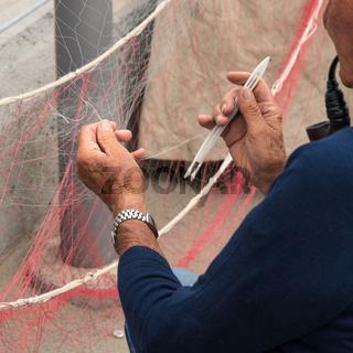 Fisherman is fixing a fishing net