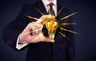 business person holding an electric light bulb