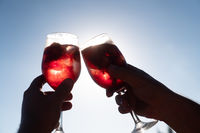 Closeup of hands toasting with glasses of Sangria with red wine