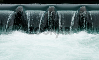 close up of a manmade concrete weir in a city with a blue river cascading over it