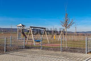 Eingezaeunter Spielplatz neben einem Kindergarten