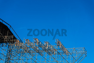 Metallic structure of assembled pipes to hold a stage, blue sky background.