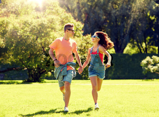 happy teenage couple running at summer park
