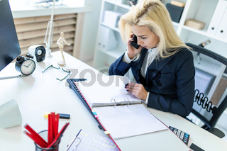 Young girl sitting at desk in office, talking on phone and looking at documents.