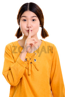 Studio shot of young beautiful Asian woman with finger on lips