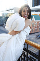 Portrait of smiling beautiful woman with white blanket