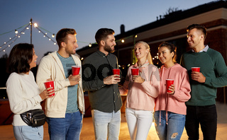 friends with drinks at rooftop party