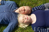 young couple laying on grass side by side
