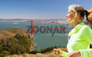 woman with earphones running over san francisco