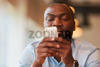 Afrikanischer Mann mit Smartphone liest SMS
