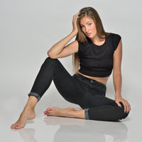 Sexy beautiful woman in black sitting on the floor