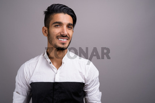 Young handsome Persian businessman against gray background