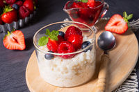 delicious milk rice with different berries and red fruit jelly