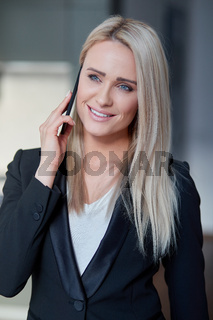 Smiling blonde middle age woman, managing director having smartphone conversation