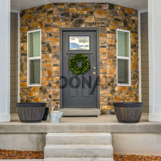 Square Glass paned front door and windows on the half hexagon shaped wall of a home