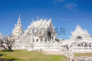 Bridge of 'the cycle of rebirth' and the ornate building of White Temple in a bright day. Chiang Rai province, Thailand