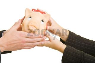 Hände überreichen Sparschwein
