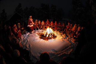 Weihnachtsmaenner sitzen im Kreis um ein Lagerfeuer, Gaellivare