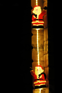beleuchtete Weihnachtsmaenner haengen an einer Hausecke