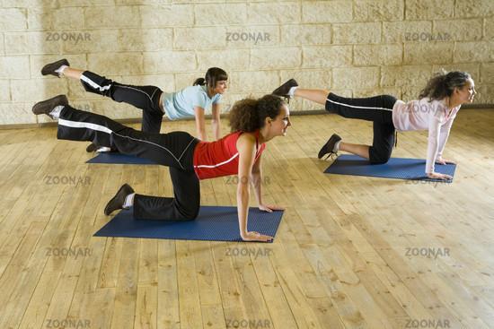 Women making stretching exercise on mat