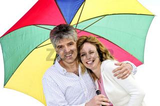 Happy mature couple with umbrella