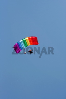 Parachuter with colored parachute on sky background 3