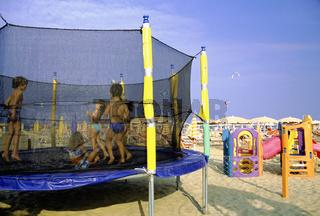 Rimini beach Emilia Romagna Italy, Children bouncing on trampoline on beach