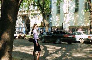 Ukraine, Odessa, woman standing on sidewalk, side view