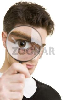 Mann schaut durch Lupe
