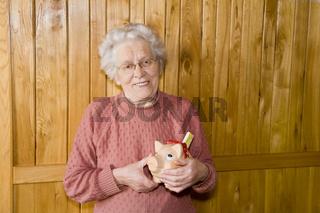 Seniorin mit Sparschwein