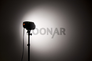 small studio flash throwing a spotlight on the wall