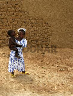 Kleines Mädchen mit Schwester auf dem Arm