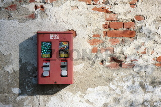 a chewing gum dispenser on a battered wall