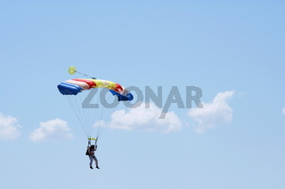 Parachuter on the cloudy sky background