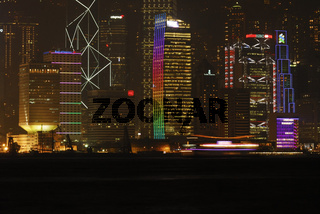 bunt beleuchtete Hochhaeuser auf Hongkong Island mit vorbeifahrendem Schiff