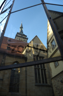 Die Stiftskirche spiegelt sich in einer modernen Glasfassade