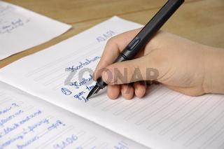 Kind macht Englisch-Hausaufgaben   Child is doing his homework