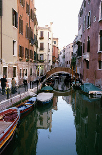 Narrow canals Campo Frari, Boats in canal with reflection between buildings, bridge in background, Venice, Italy