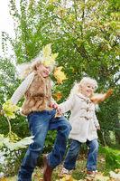 Zwei Mädchen spielen mit Blättern